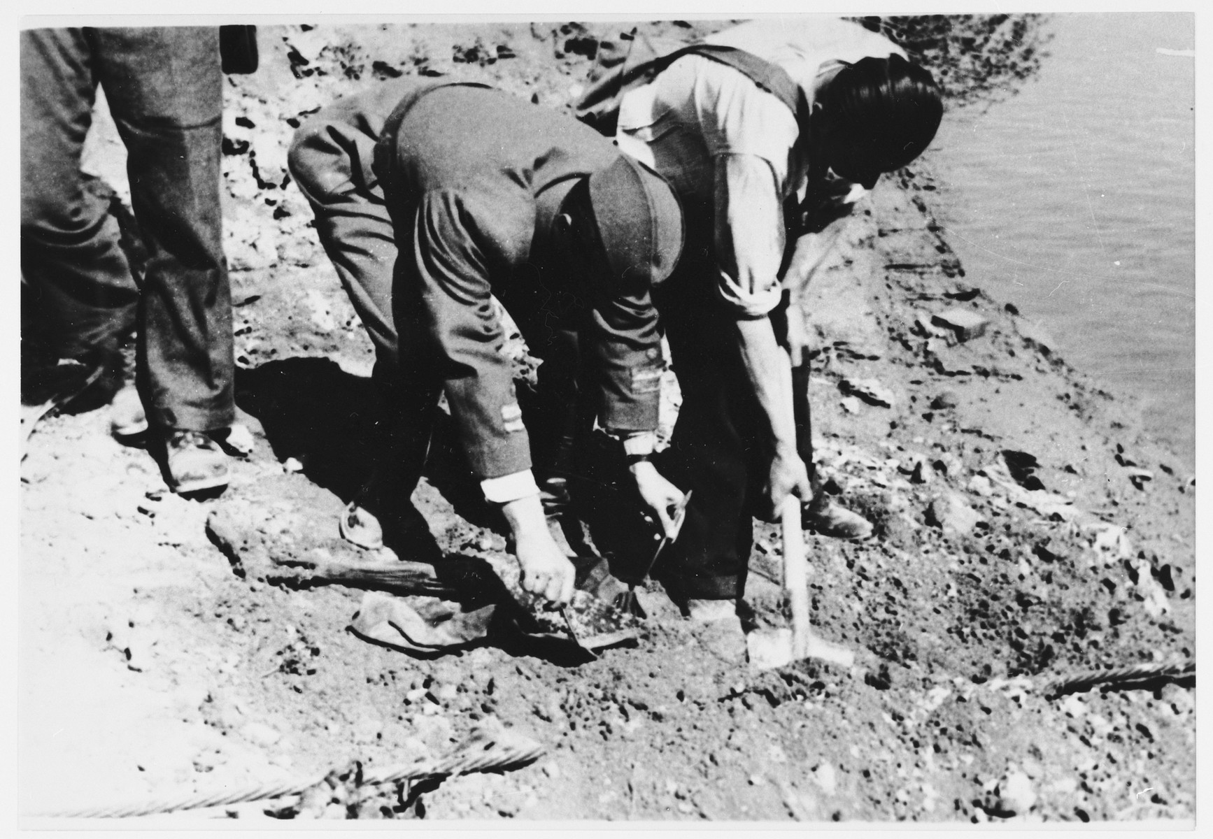 Members of the first Yugoslav war crimes commission investigating atrocities at the Jasenovac concentration camp, collect evidence on the banks of the Sava River.