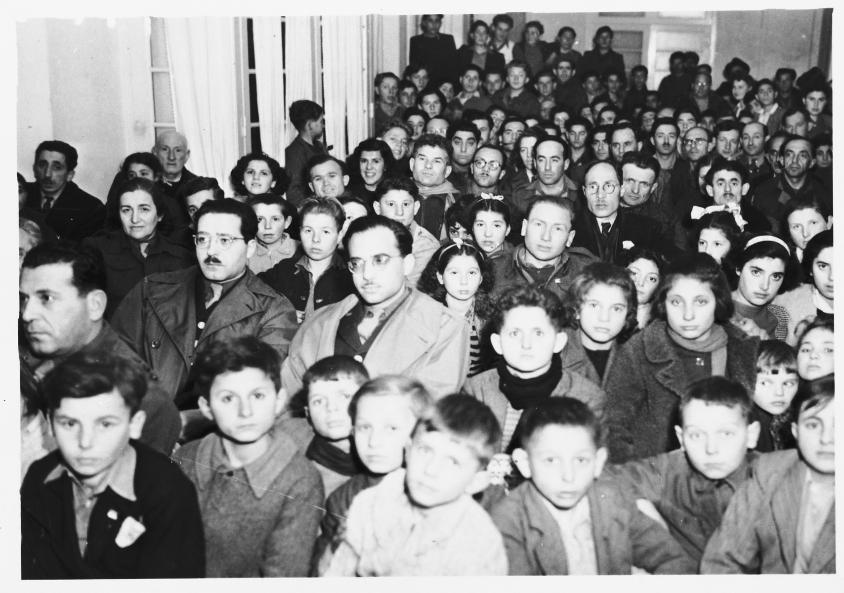 A large group of children crowds into the auditorium of the Selvino Youth Aliyah children's home.