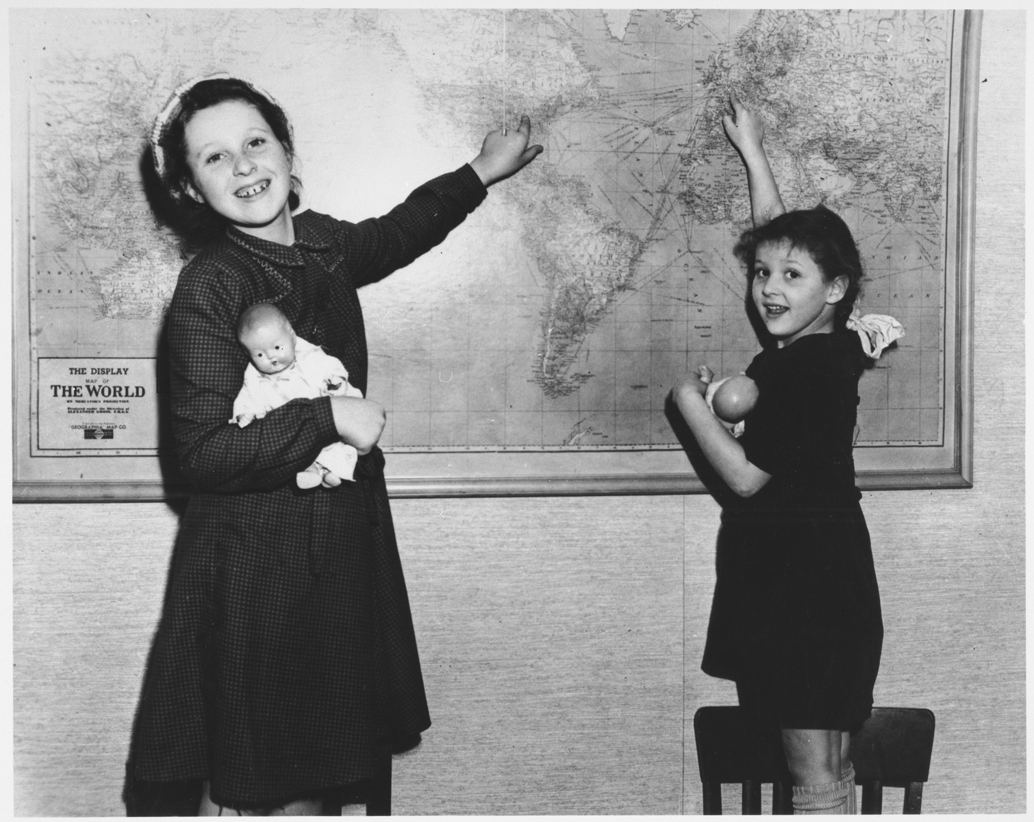 Two Jewish sisters, Dora and Marie Claire Rakowski point out their journey to America on a wall map soon after their immigration to the US.  This photograph was published in the Agudat Yisrael newspaper along with an article describing how the organization was sponsoring their immigration.