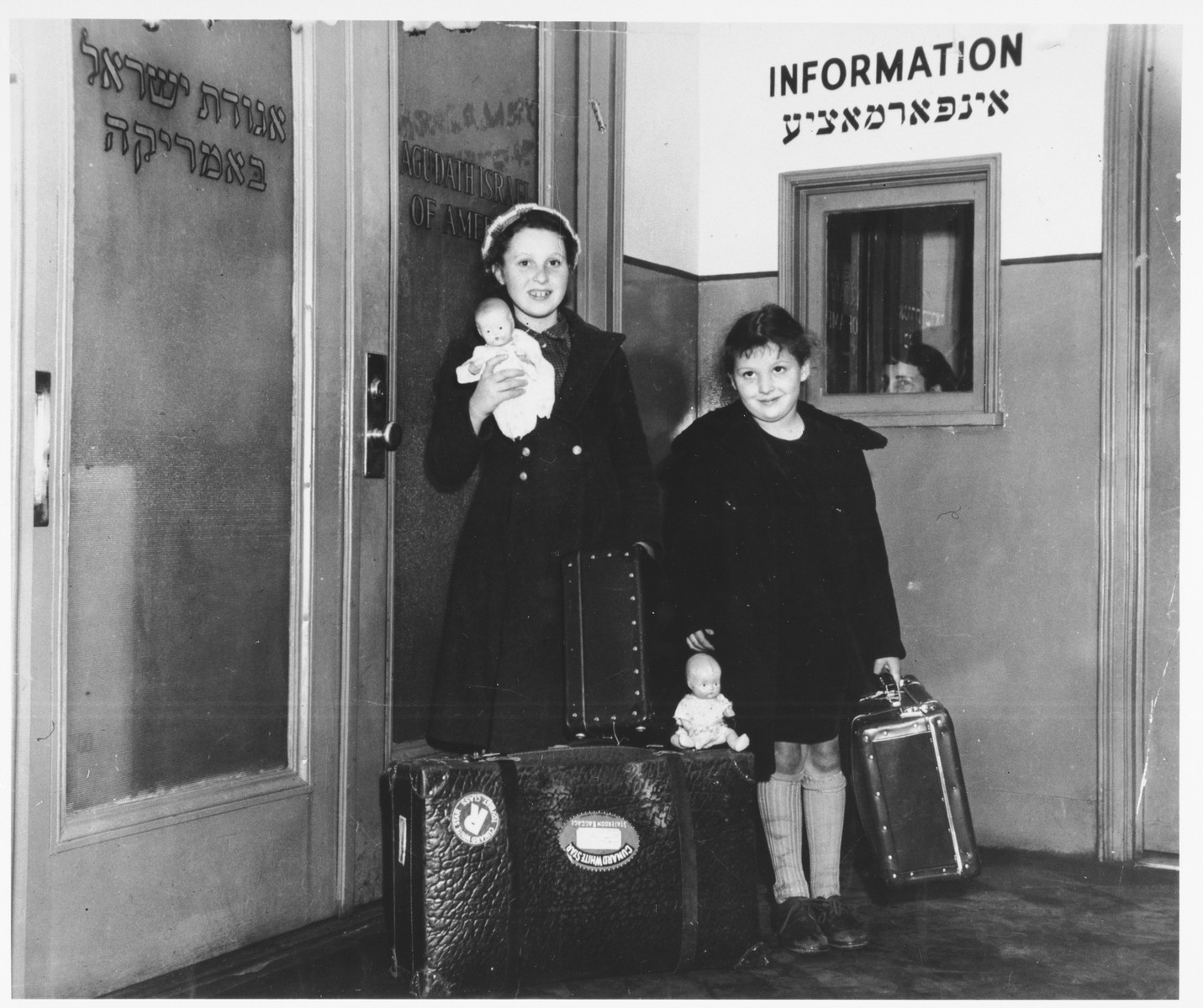 Two Jewish sisters, Dora and Marie Claire Rakowski, arrive at the offices of the Agudat Yisrael in New York holding new dolls and their suitcases.