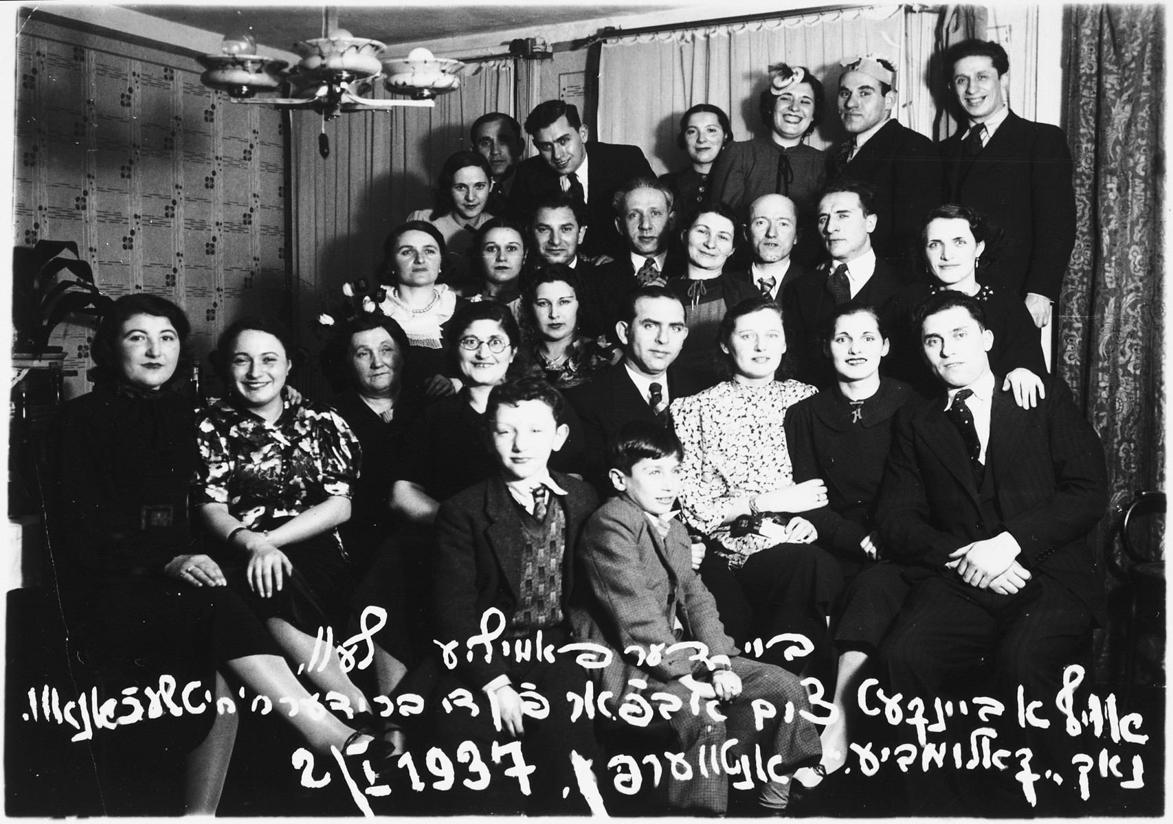 Group portrait of family and friends attending a banquet to mark the departure of the Ciechanow brothers, Alex and Adolf, for Colombia.  Among those pictured is Alex Ciechanow (bottom, right), Leah Ciechanow (behind Alex), Rochelle Ciechanow (front row, third from the right), Monek Lublin (front row, fourth from the right), Jackie Ciechanow (boy in the front row, center), Mendel Olszyn (second row from the top, center).  Also pictured are Estera and Adolf Ciechanow and Chana (Ciechanow) Olszyn.