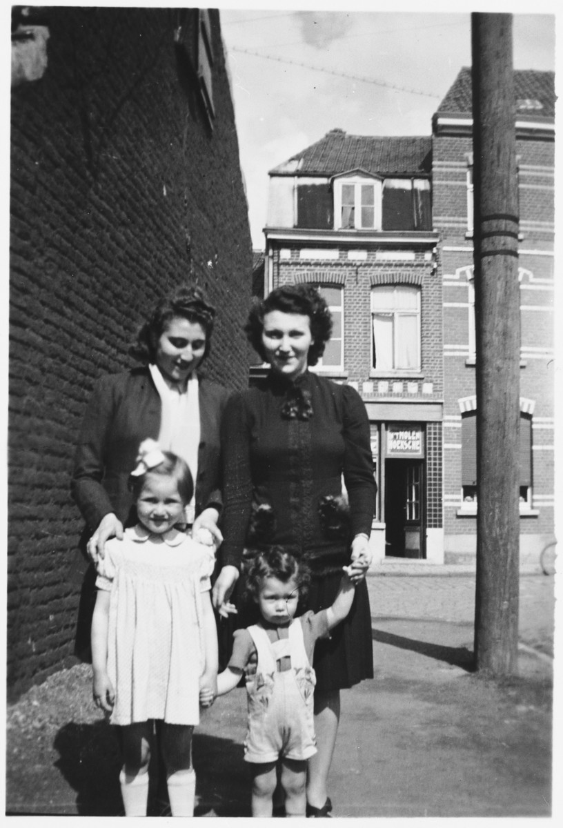 A Jewish family poses on a street in Courtrai while in hiding.  Pictured are Lea Obstfeld and her son, Norbert, her sister, Emily Zwaaf and her niece, Jacqueline.