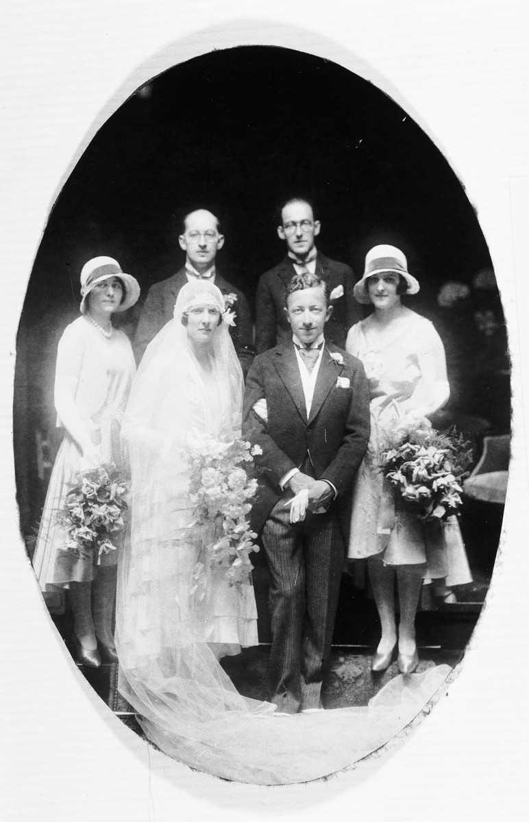 Group portrait of members of the wedding party at the marriage of Paul and Berthe Hendrix.  Pictured from left to right behind the bride and groom are: Dinie Hendrix (the groom's sister), Samuel Vles and Nico Vles (cousins of the bride), and Dora Reuder-Vles (the bride's aunt).