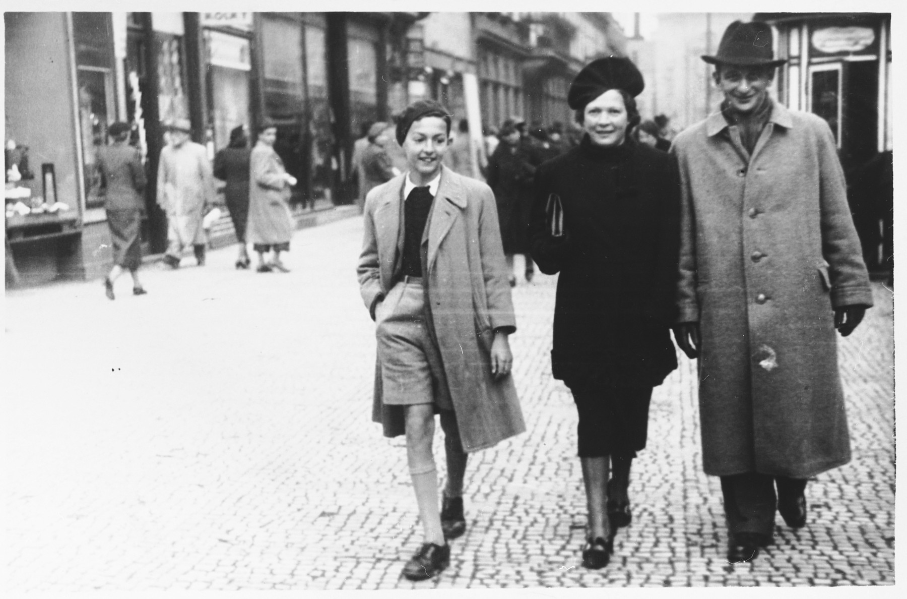 Austrian Jewish refugees walk along a street in Prague.  Pictured from left to right are Alfred and Trimette Langer.  The man on the right is unidentified.