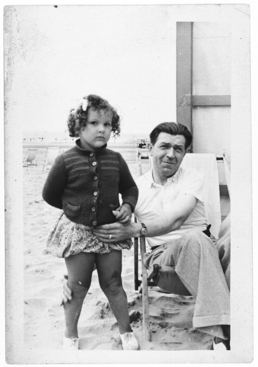 "A Jewish child poses with her Belgian rescuer on a beach in Belgium.  Pictured are Marie Claire Rakowski and ""Papi"" Hicket."