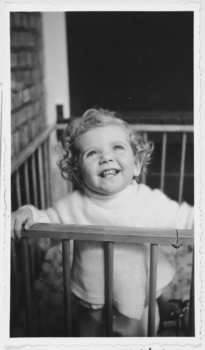 A young Jewish girl stands in a playpen in her parent's home in Amsterdam.  Pictured is Marianne Hendrix.