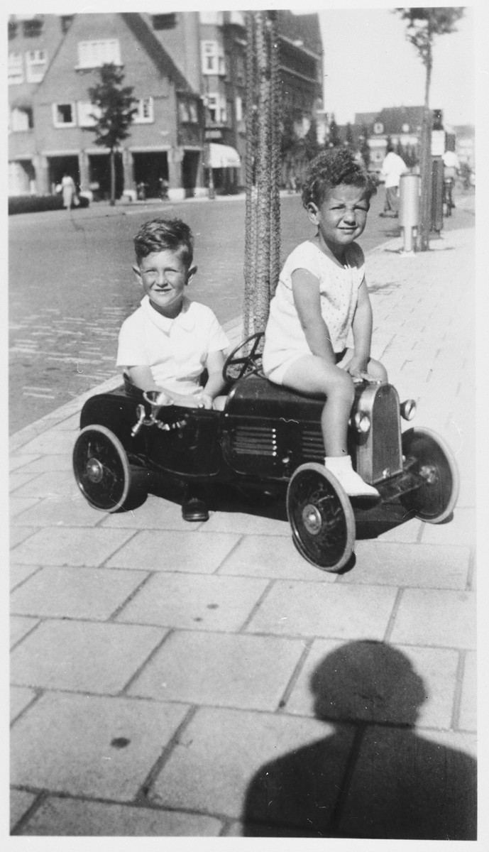 Two young Jewish boys ride a toy car on a sidewalk in Amsterdam.  Pictured are Robert and Hans Hendrix.
