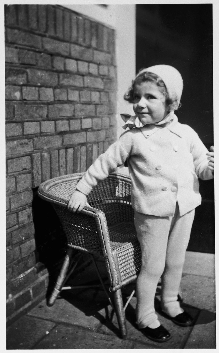 A young Jewish girl who is living in hiding in the home of her aunt and uncle, poses next to a wicker chair.  Pictured is Marianne Hendrix.