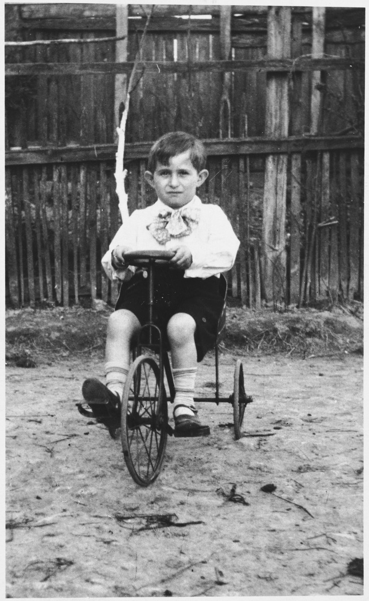 Dov Zugman rides his tricycle in a yard in Sokol.