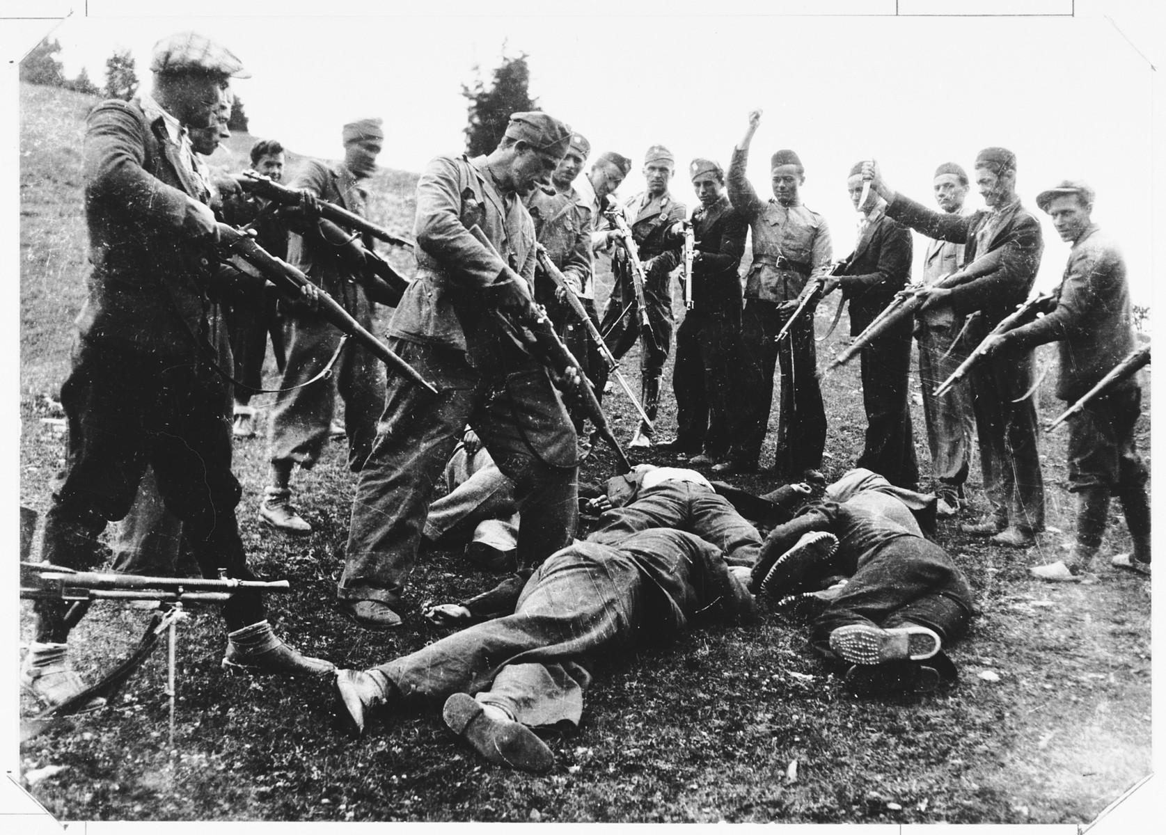A unit of Ustasa militia point their rifles at a group of bodies lying at their feet.