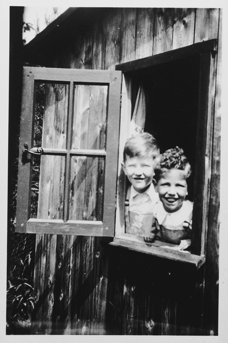 Two young Jewish brothers peer out from a window of a wooden cabin.  Pictured are Robert and Hans Hendrix.