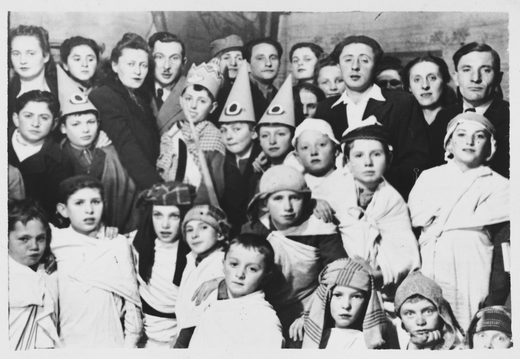 Children attend a Purim costume party in the Foehrenwald DP camp.  Those pictured include Chaim Swidler, Roman Haar and Barry Golub.  The principal Mr. Biber is on the right, and a teacher Mr. Zektzer is in the second row on the far left.