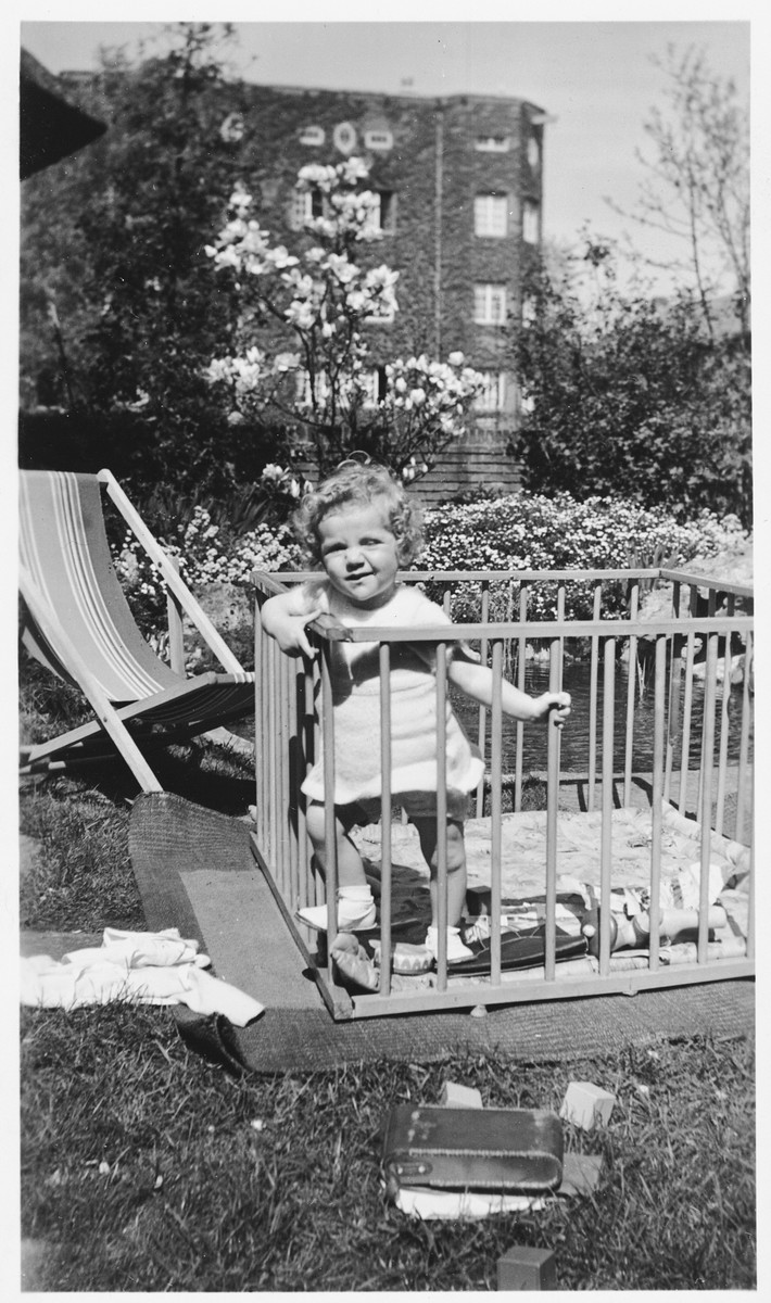 A young Jewish girl stands in a playpen in the yard of her parent's home in Amsterdam.  Pictured is Marianne Hendrix.
