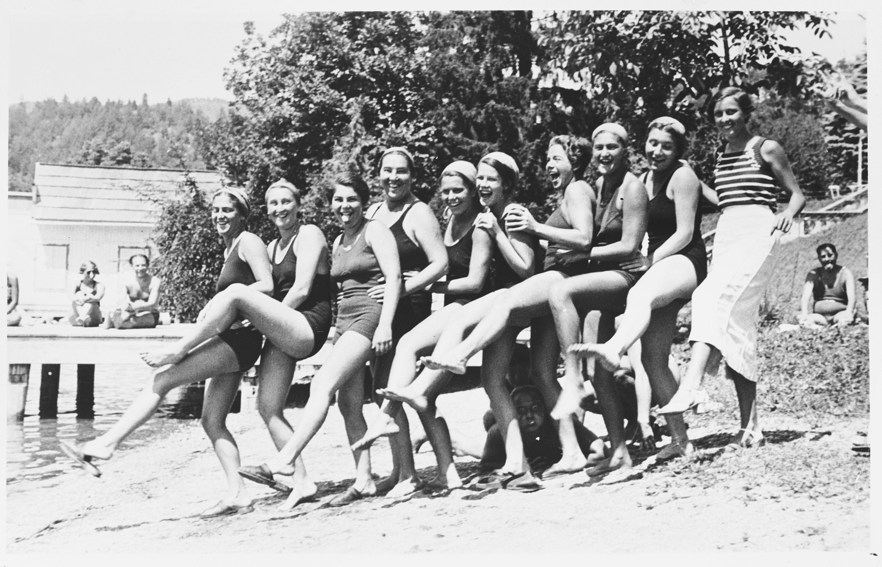 A group of female swimmers pose on the beach.  Among those pictured are: Ruth Langer (third from the right), Anna-Marie Pick (second from the right), and Judith Deutsch (sixth from the right).