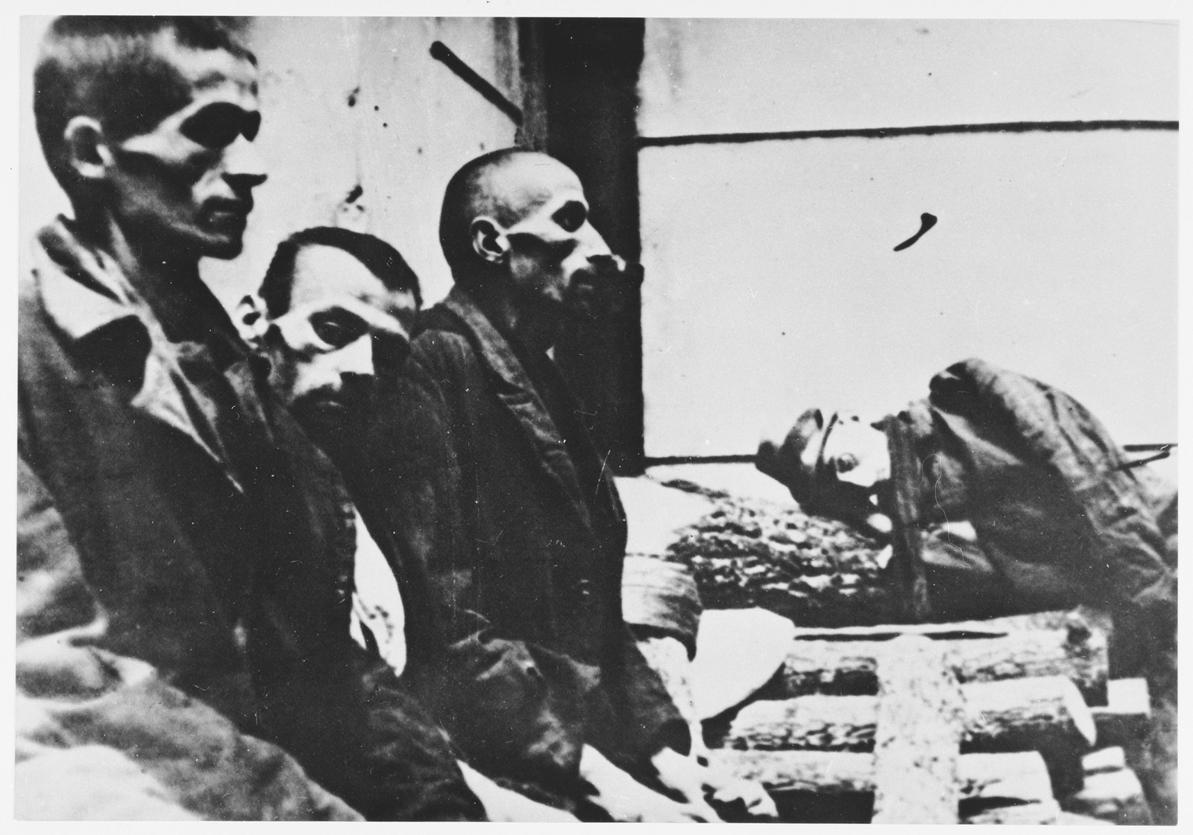 """Four male survivors of the Jasenovac concentration camp.  The handwritten caption reads, """"This was the appearance of people after they left Ustasa camp Jasenovac."""""""