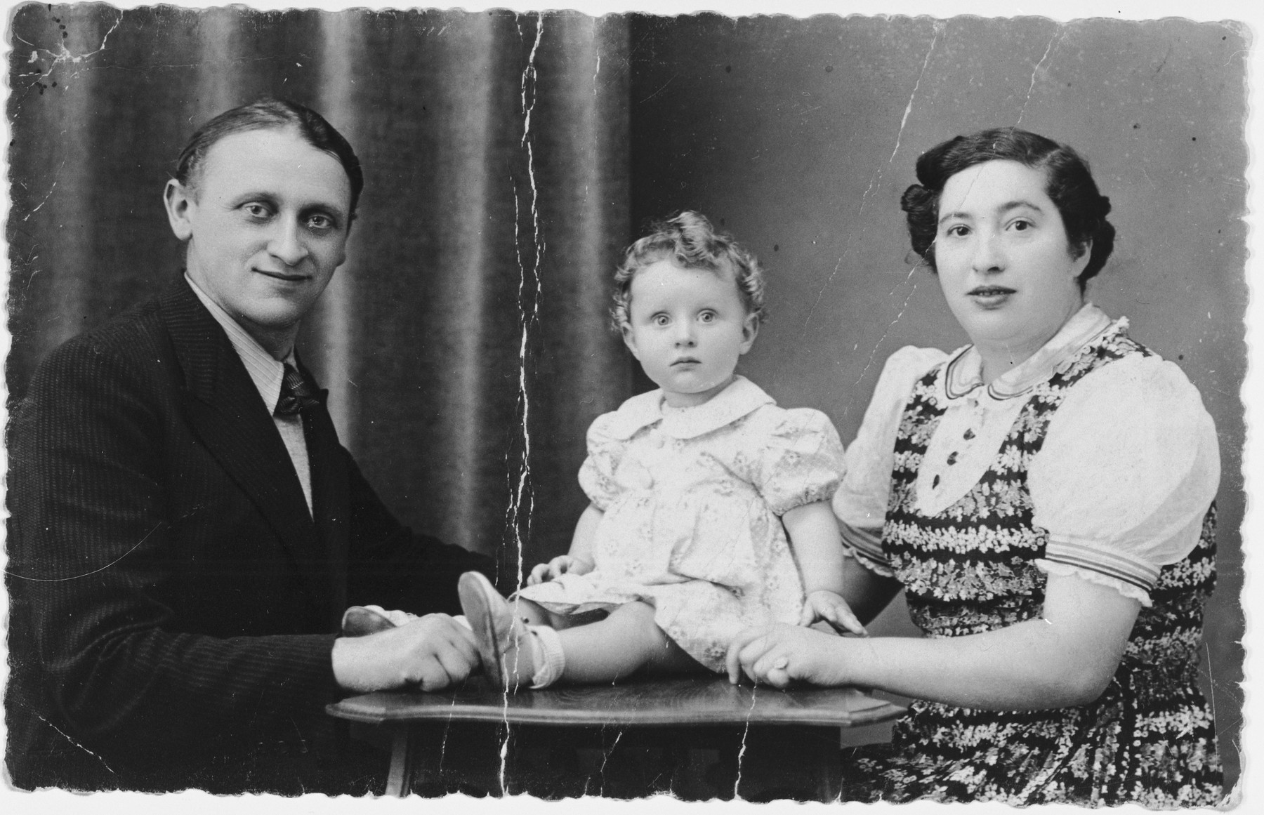 Studio portrait of the Rakowski family in Brussels, Belgium.  Pictured are Ephraim and Blima Rakowski with their infant daughter, Marie Claire, shortly before the child was placed in hiding.