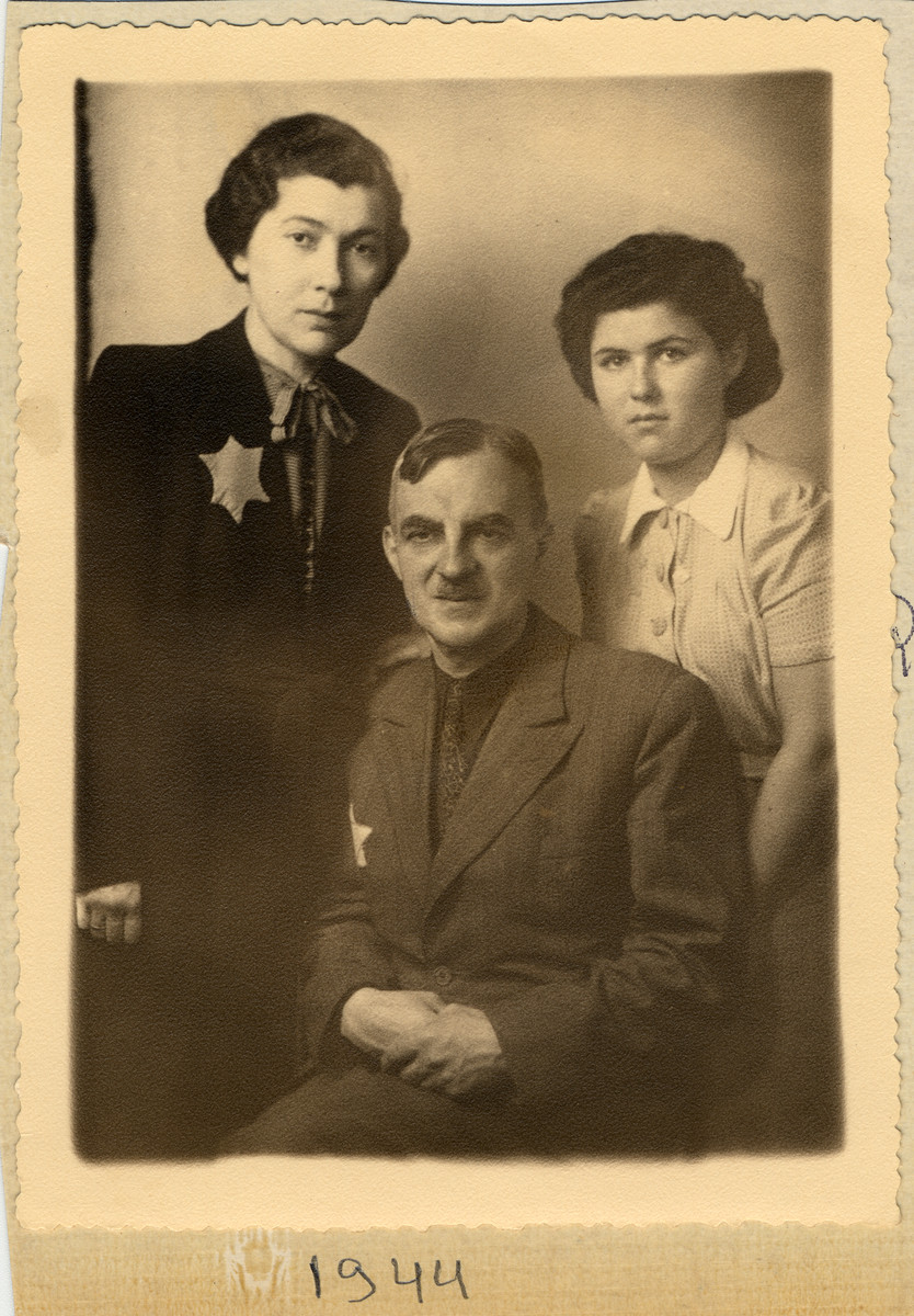 Studio portrait of a family in the Lodz ghetto wearing yellow stars.  Pictured are Dora, Gustaw and Inka Gerson.