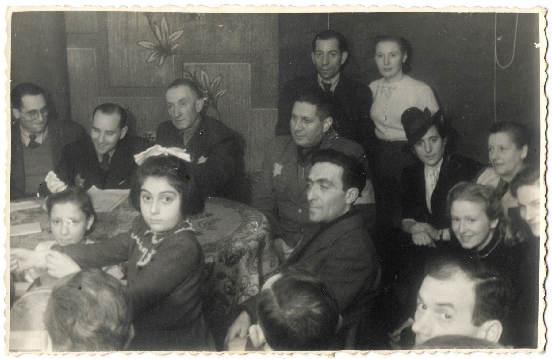 A large group of adults and children gathers together inside a room in the Lodz ghetto.  Among those pictured is Ruth Berlinska (front wearing a bow in her hair).
