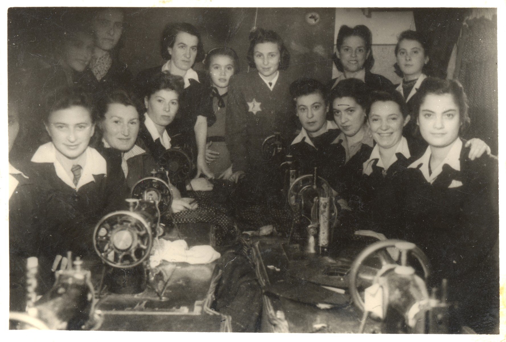 Group portrait of teenage girls and teachers wearing Stars of David in a sewing workshop in the Lodz ghetto.