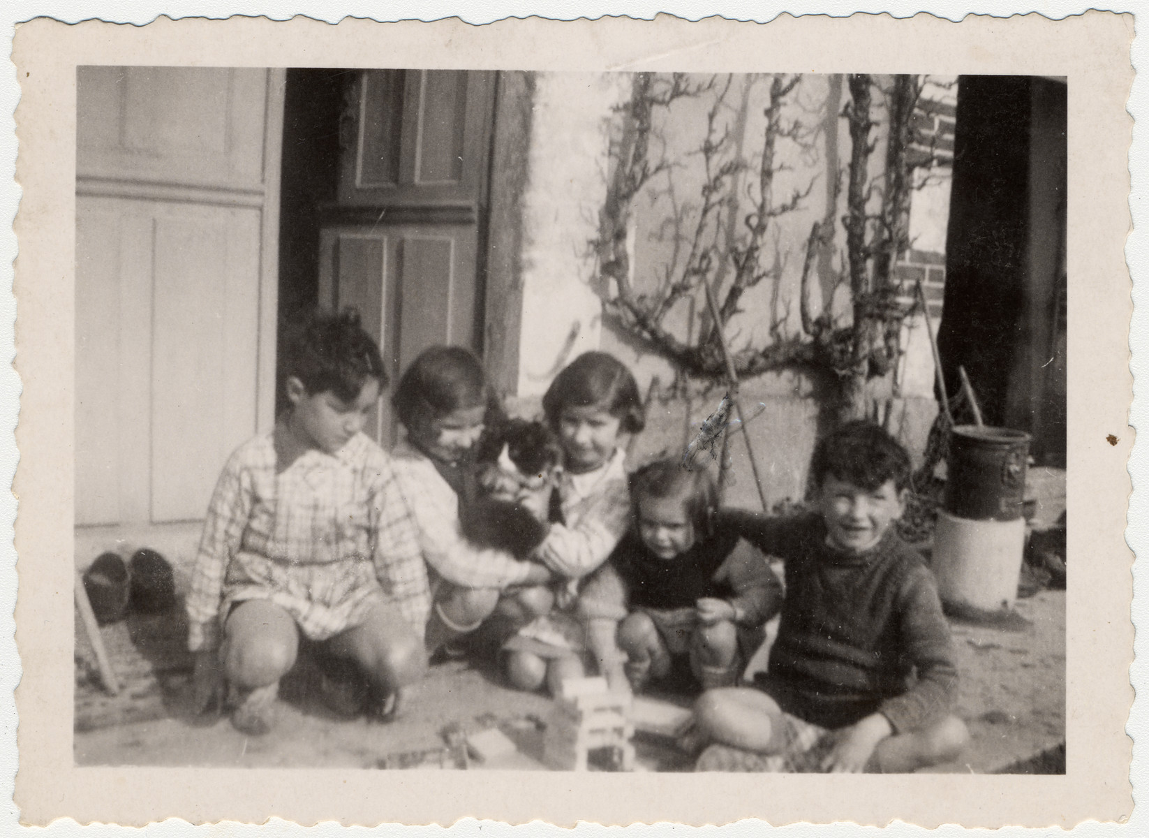 Steven Simon at left with another Jewish child at right playing with the three daughters of a Quaker staff family in front of a Quaker residence, Moulin de la Ferriere, Noce, Normandy in early 1040, after being evacuated from Paris because of German bombing.