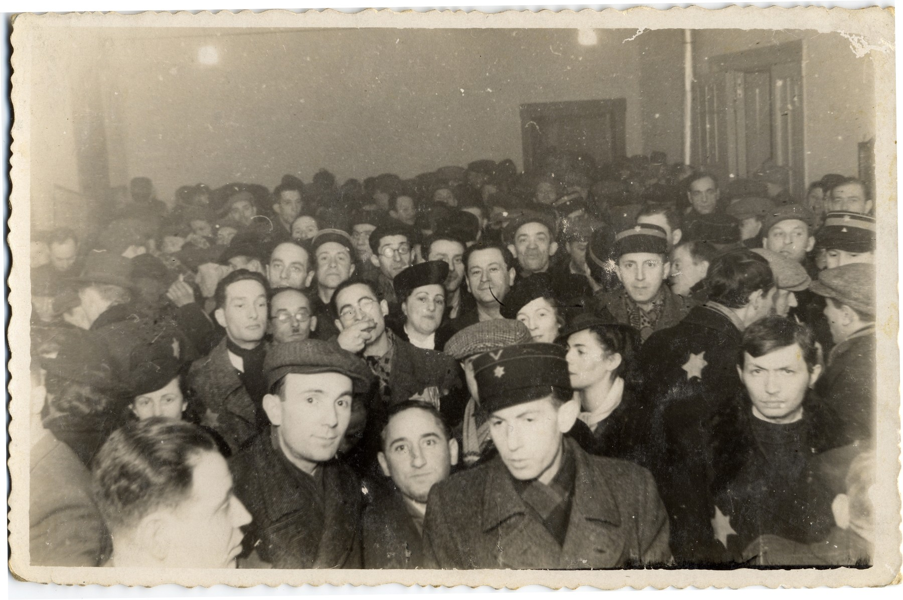 Jewish men and women wearing Stars of David, including several policeman, crowd together in a hall in the Lodz ghetto.