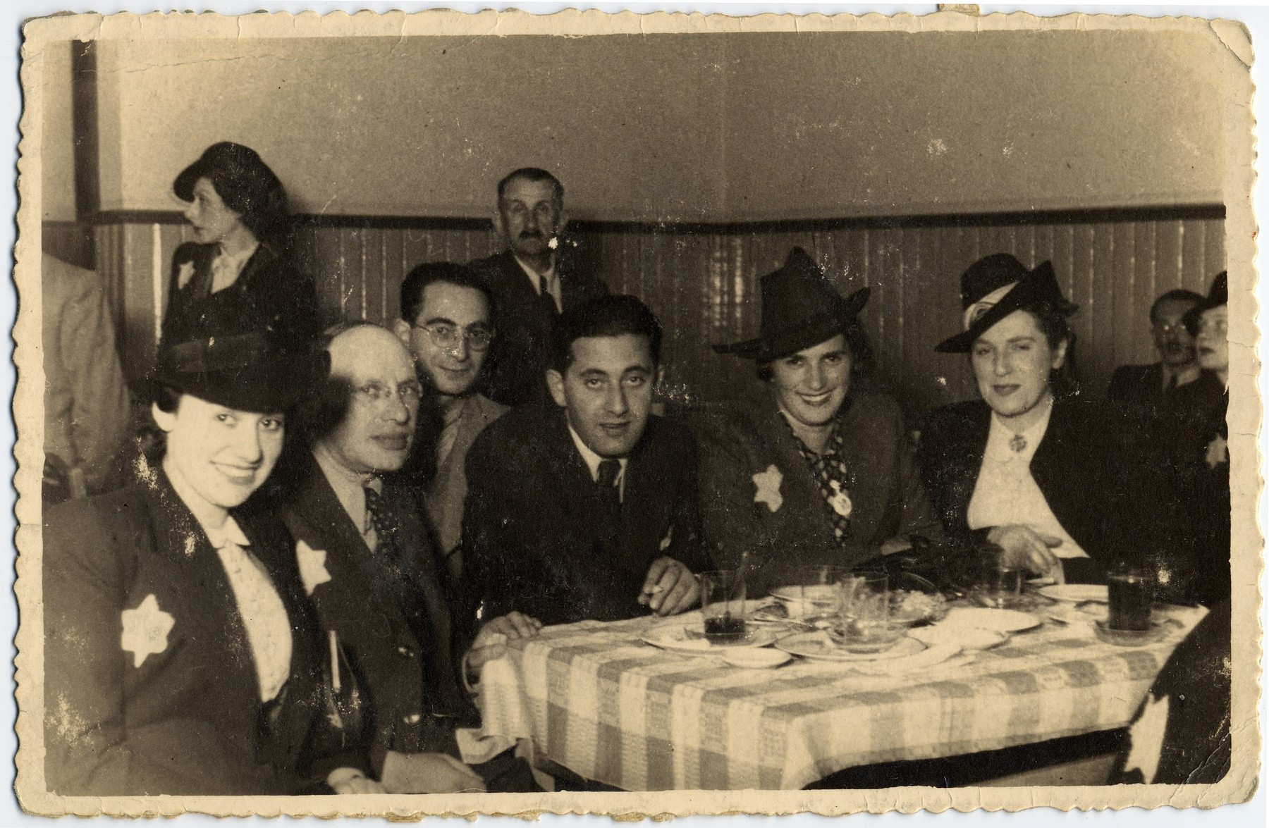 Group portrait of Jewish men and women in a cafe in the Lodz ghetto.   Pictured from left to right are: Dora Fuks (Rumkowski's secretary), David Warszawski (director of the tailoring workskops), Leon Fajtlowicz (in the back, donor's maternal uncle, in charge of the leather workshops), Aron Jakubowicz? (director of workshops), Regina Jakubowicz and unknown.