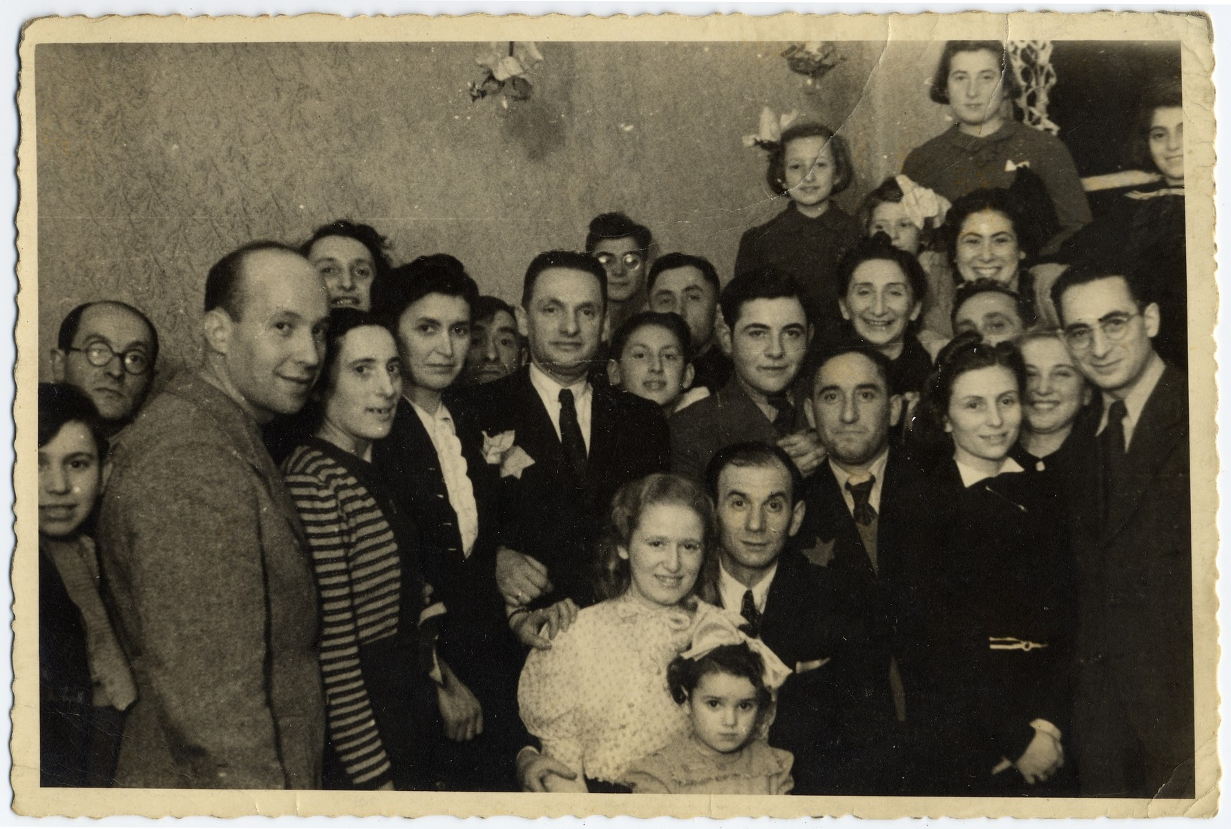 Group portrait of adults and children in the Lodz ghetto.   Among those pictured is Leon Fajtlowicz (front, right) and next to him his wife, Cesia Golab Fajtlowicz (?).  Leon was the uncle of the donor and in charge of all the leather workshops in the ghetto.
