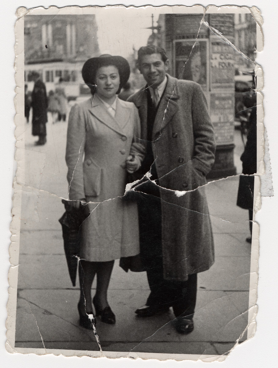 Street portrait of a Jewish couple in Belgium standing in front of a kiosk taken less than a year before they were deported to Auschwitz.  Pictured are Brucha (Bertha) Mechlowitz and her husband Heinrich (Henry) Chutz.