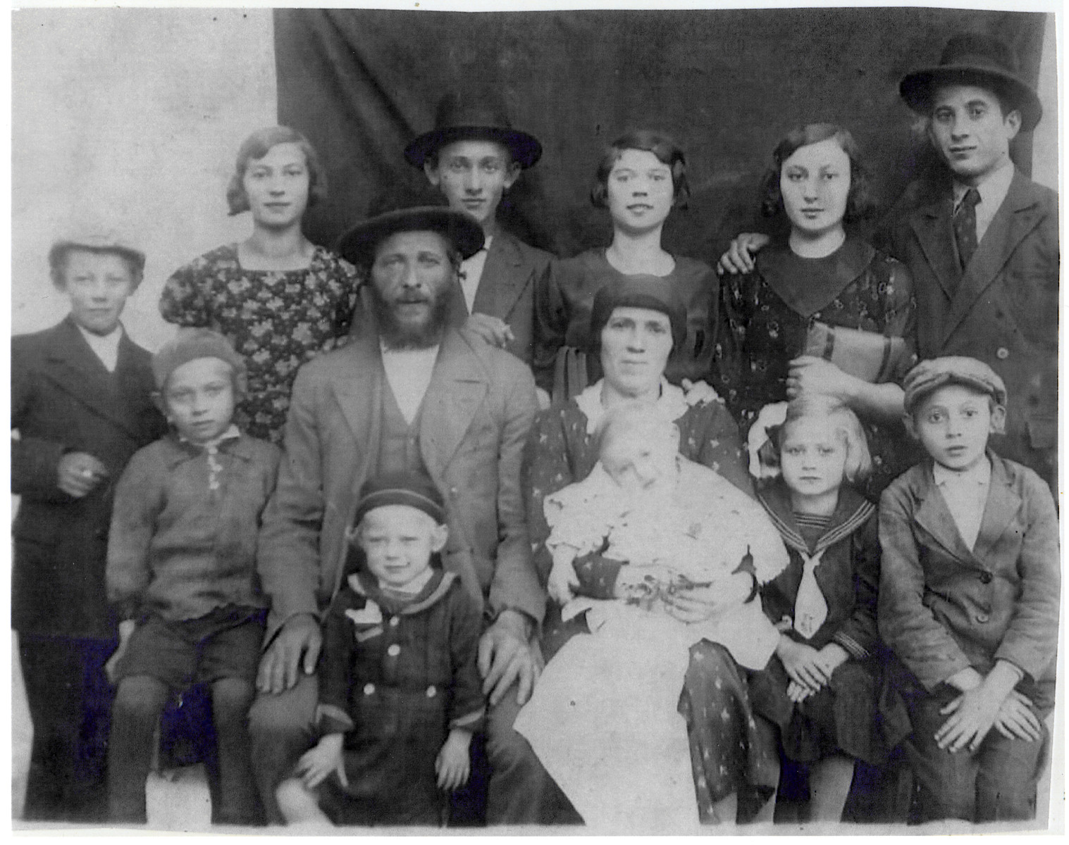 """Portrait of a large, religious Transcarpathian Jewish family.  The oldest daughter had moved to Holland and just gotten engaged.  She came home to visit her family and arranged for the photo to be taken to show her fiance.  Pictured are the Mechlovitz family.  Seated left to right are Baruch, Chaim, (name of child between his legs is unknown), Etel holding a baby (name unknown), Pearl and Alter.  Standing are Moshe, Baruch Zelda, Duvid Meyer, Chia Sura (Chiam's niece), Chia Hensa and Shia.   The farmer, Chaim Simcha Mechlowitz, became immortalized as the farmer in Roman Vishniac's collection """"A Vanished World."""""""