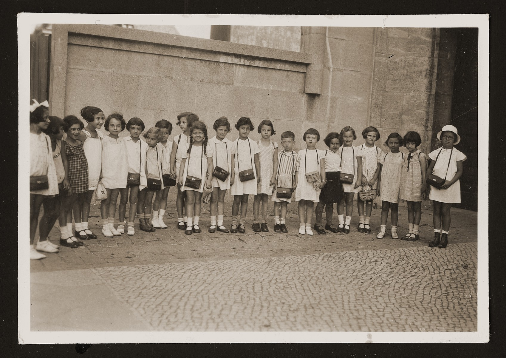 Group portrait of children in the second form at the Jewish Prinzregeuten school in Berlin as they prepare for a field trip.  Among those pictured are Anita Plachte (tenth from the right) and Mariana Waksner (far right).