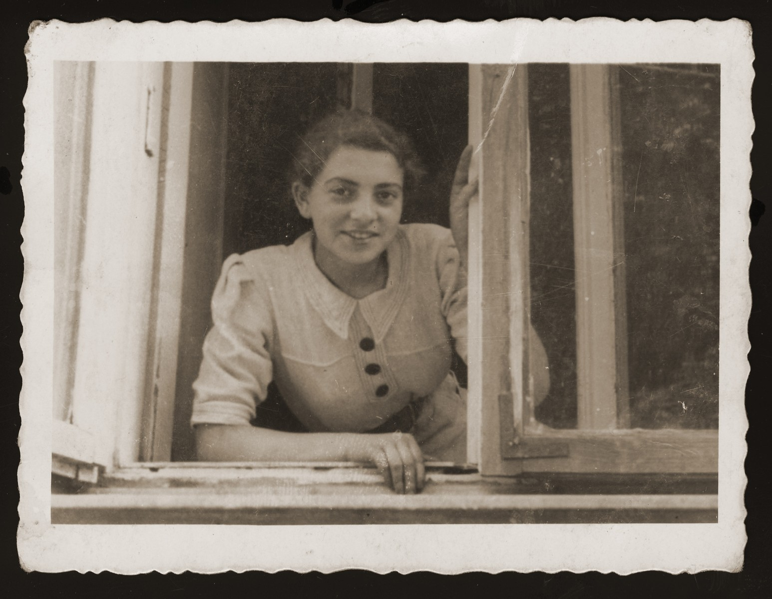 Estera Ajzen poses in the window of her home in Chelm.