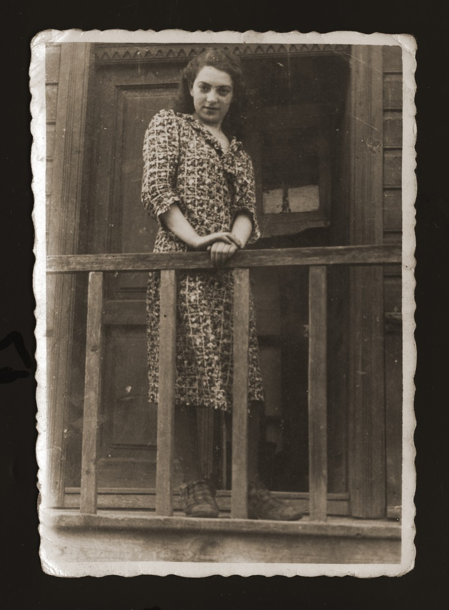 Estera Ajzen poses on the front porch of her house in Chelm.