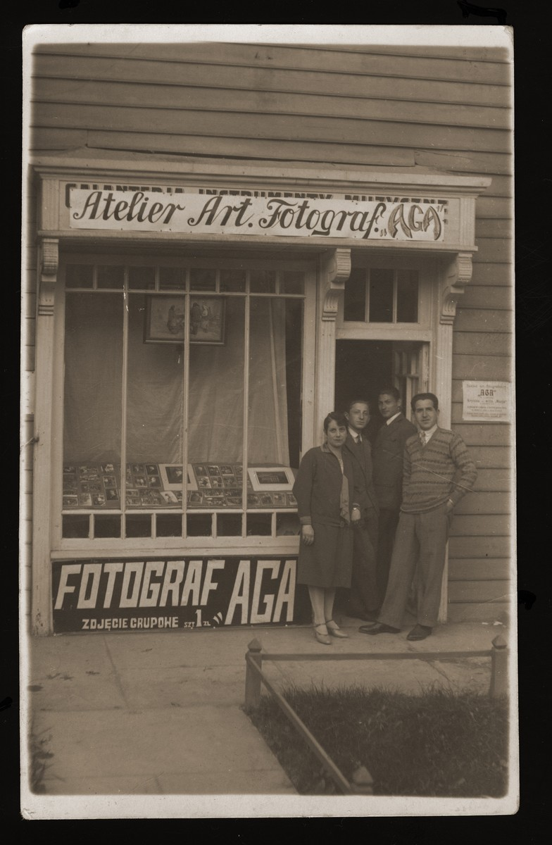 Adolph and Hania Gartenberg and two others stand in front of their photo studio in Przemysl.