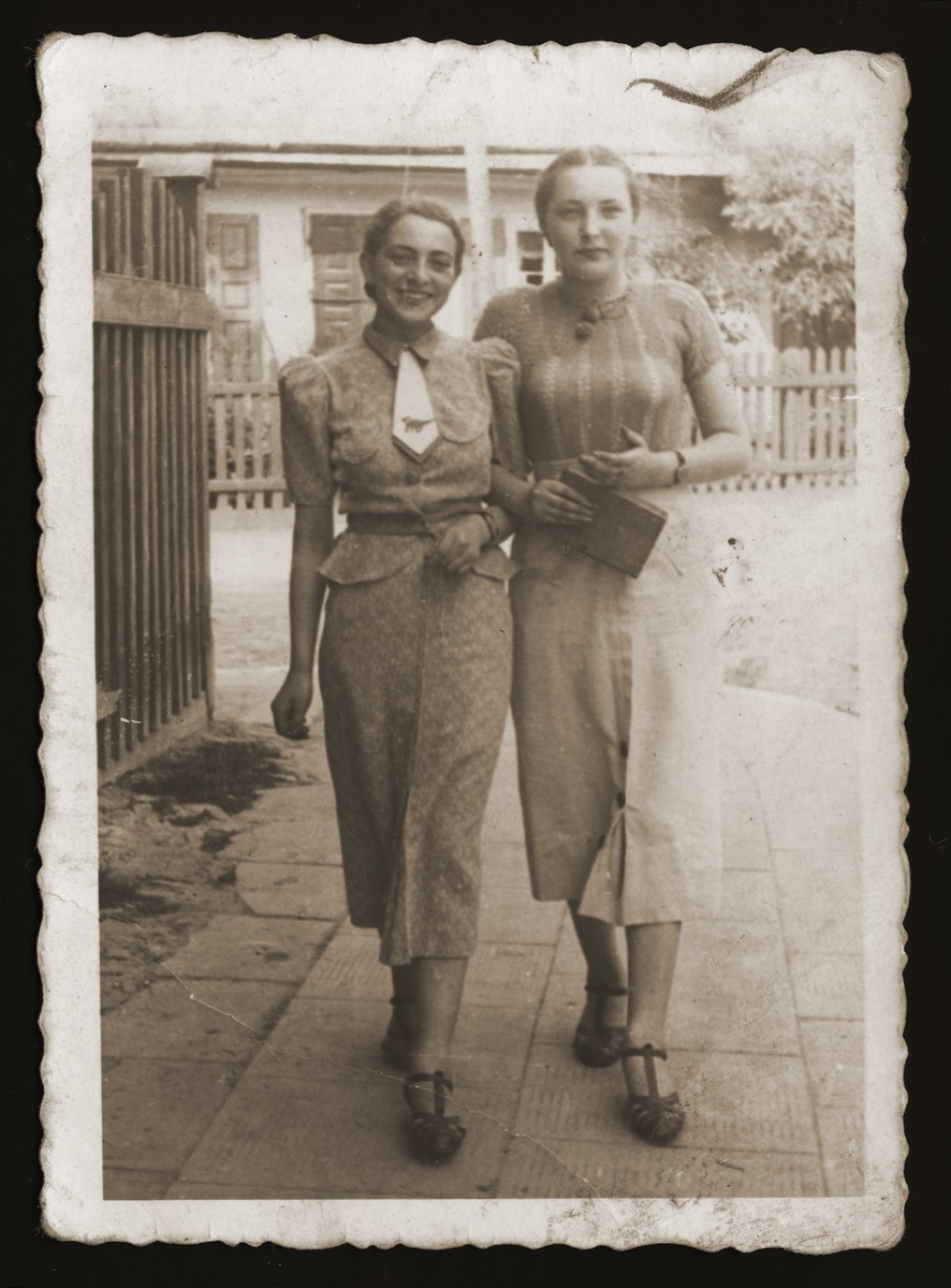 Two young Jewish women walk along a street in Chelm.  Pictured are Estera Ajzen (left) and her friend, Esterka Fiszbajn (right).