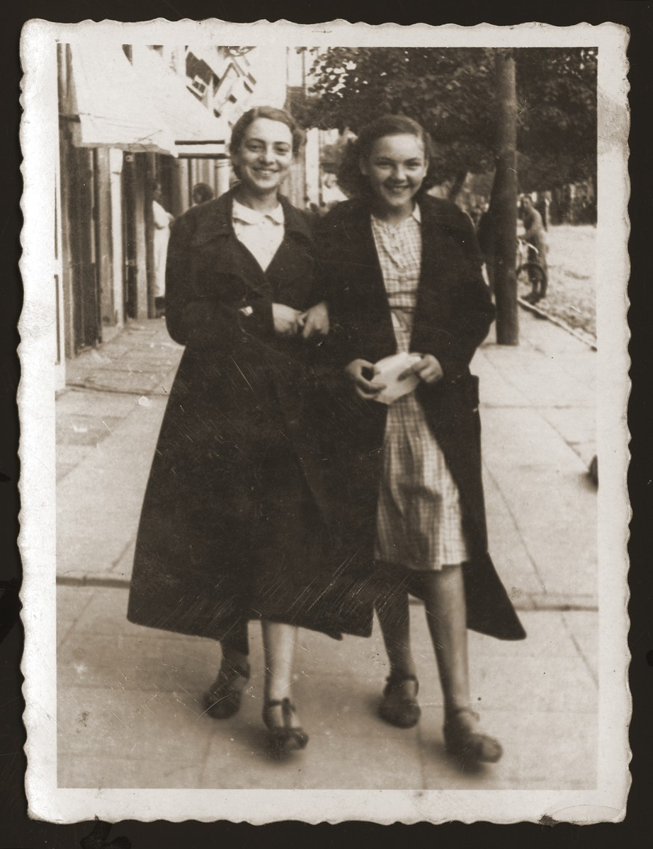 Two young Jewish women walk along a street in Chlem.  Pictured are Estera Ajzen (left) and her friend, Maniusia Wajntraub (right).