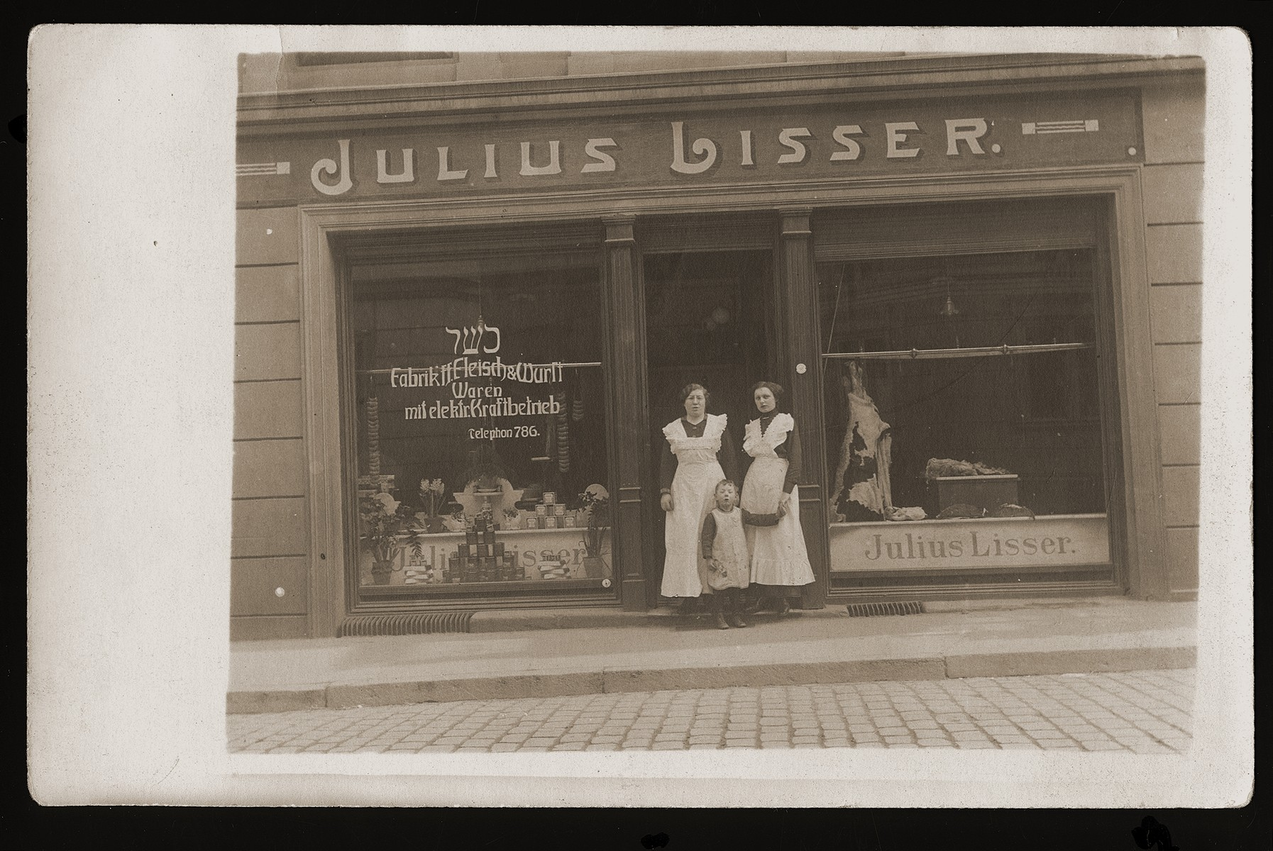 Members of the Lisser family pose in front of the Julius Lisser kosher butcher shop in Danzig.