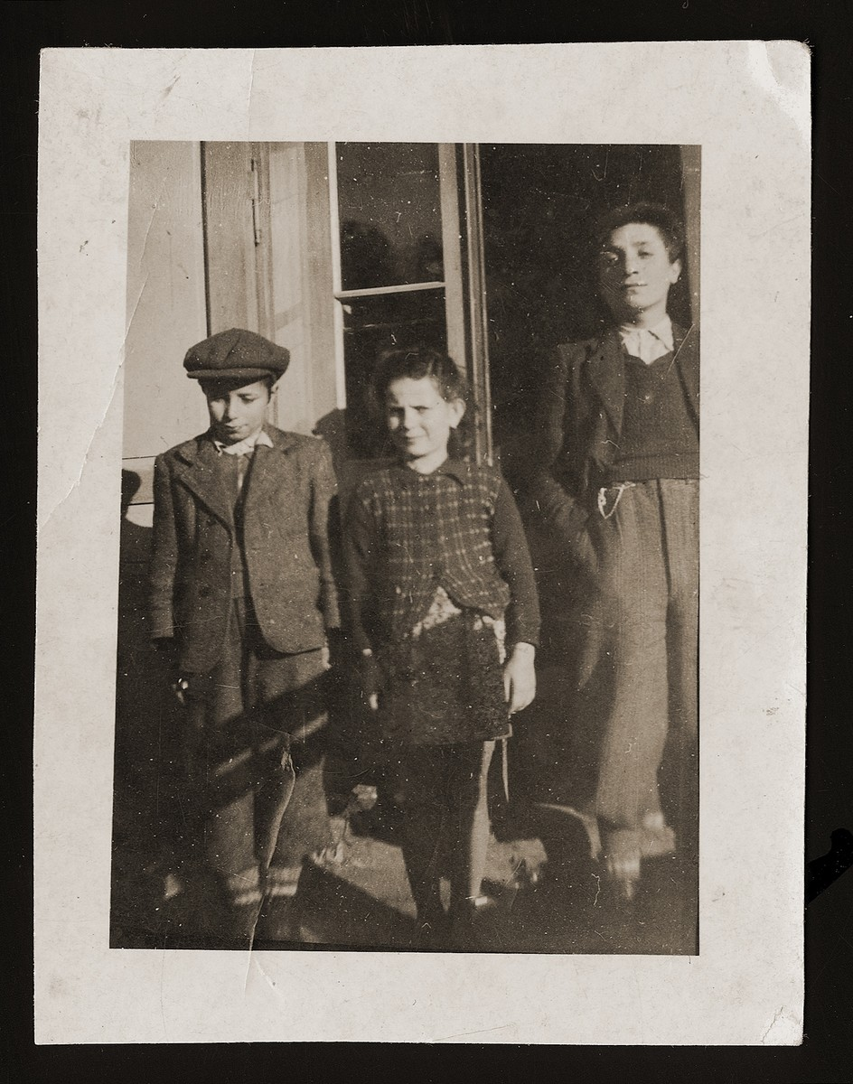 Three Jewish siblings pose on the porch of a house.  Pictured from left to right are Nachum, Jitta and Ignacz Eisner.