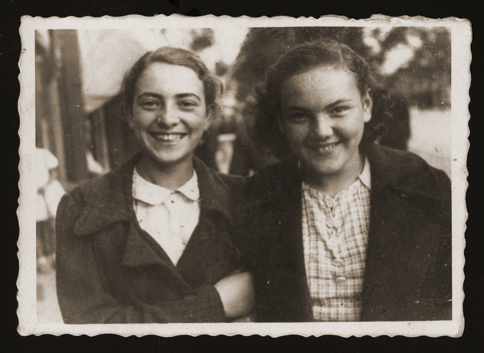 Two teenage Jewish girls pose on a street in Chelm.  Pictured are Estera Ajzen (left) and her friend, Maniusia Wajntraub (right).