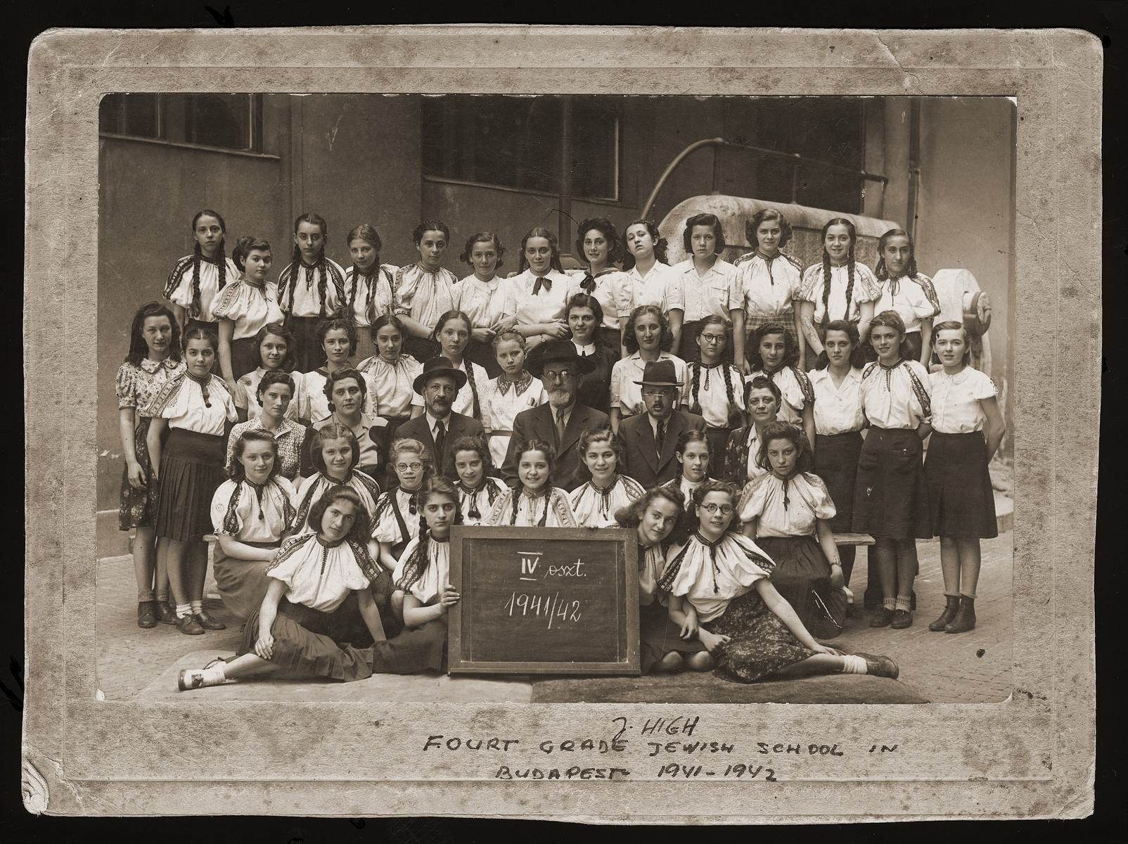Class portrait of students and teachers in the fourth grade of the Jewish high school in Budapest.  Among those pictured is Emma Guttman and Eva Rosenfeld (top row, eighth from the right).  A list of student signatures is on the verso of the photograph.