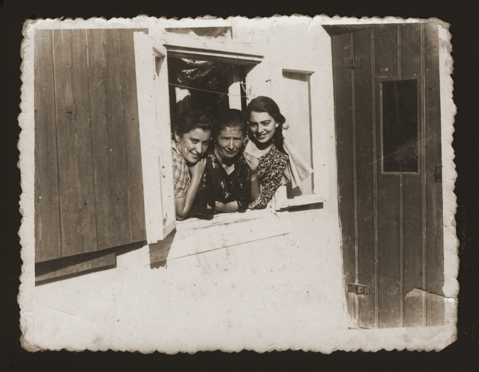 Three Jewish women look out the window of a house in Maciejow.  Among those pictured is Estera Ajzen (right) during a visit to her friend's home.