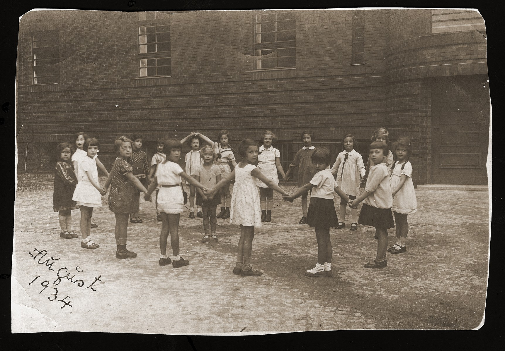 Girls in the first form of the Prinzregenten school play a circle game outside.