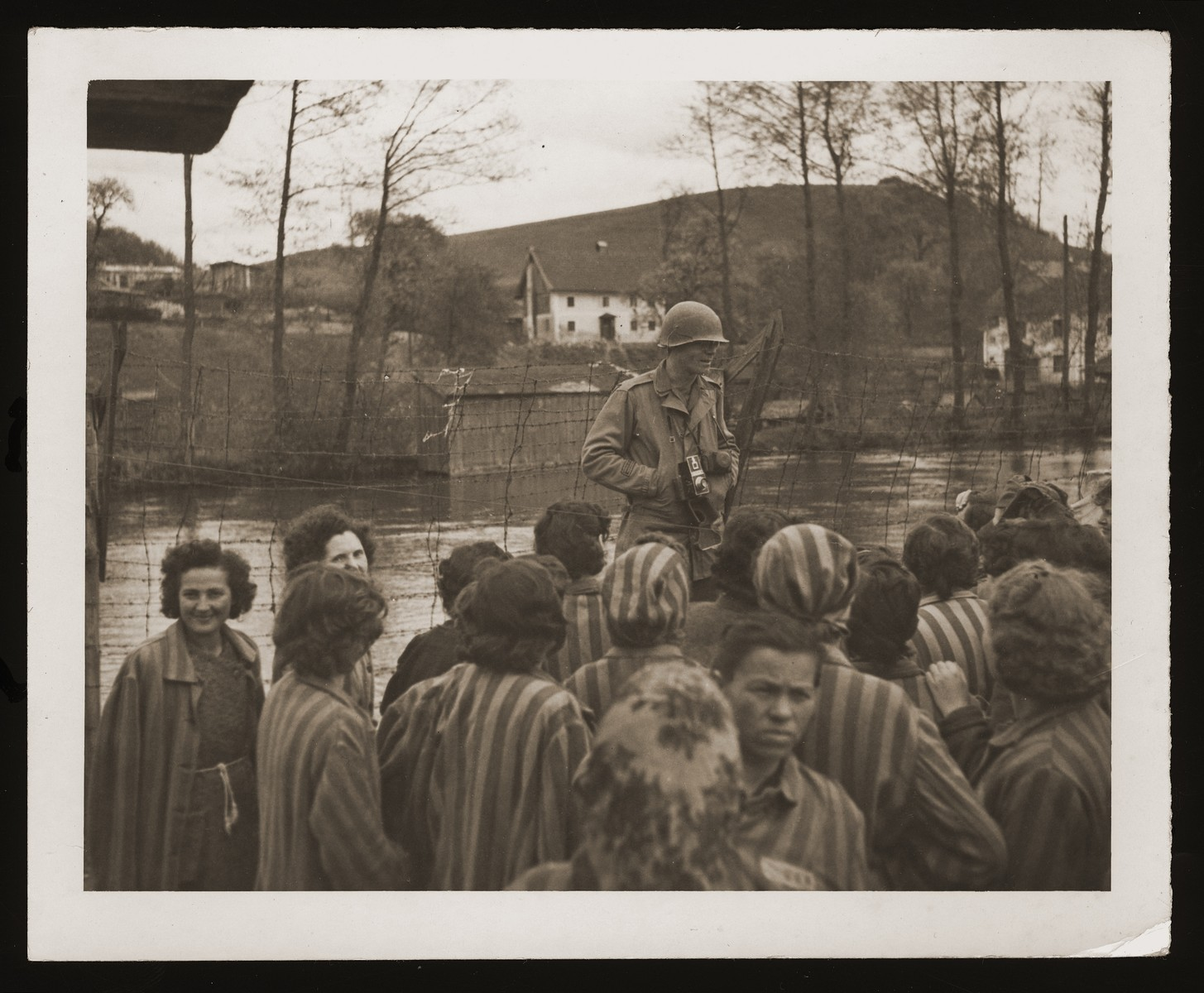 American Signal Corps photographer Sgt. Theodore Sizer of the 166th Signal Corps company, stands among a group of newly liberated, female survivors from Lenzing, a sub-camp of Mauthausen.
