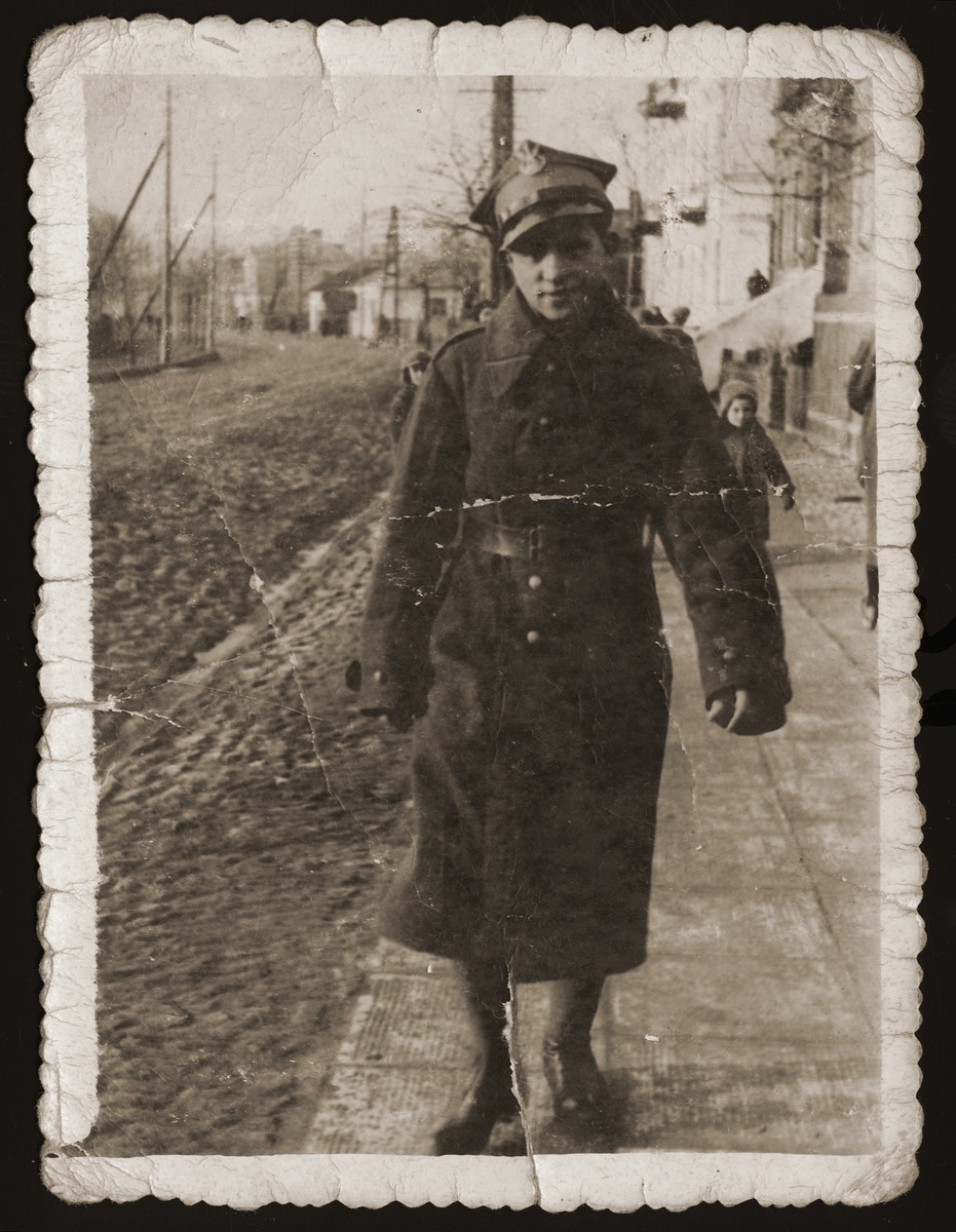 Szaja Ajzen walks along a street in Chelm in military uniform.