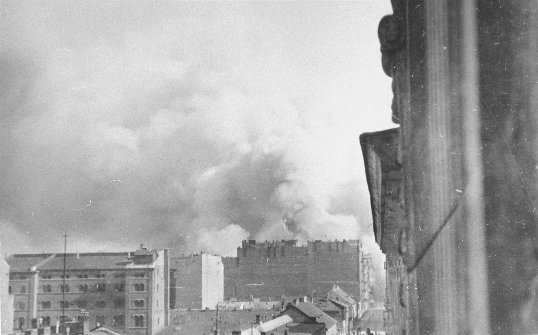 Smoke rises from buildings razed by the SS during the suppression of the Warsaw ghetto uprising.  The view is from Walicow Street looking south.