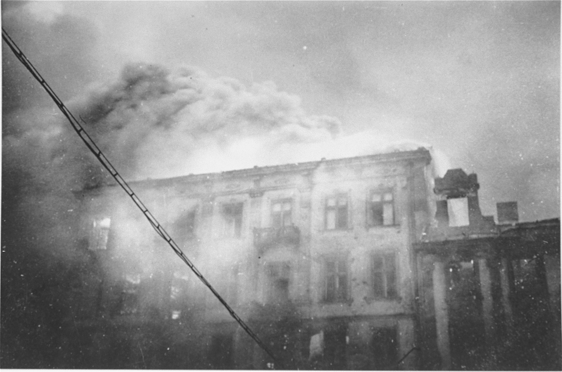 An apartment building razed by the SS burns during the suppression of the Warsaw ghetto uprising.