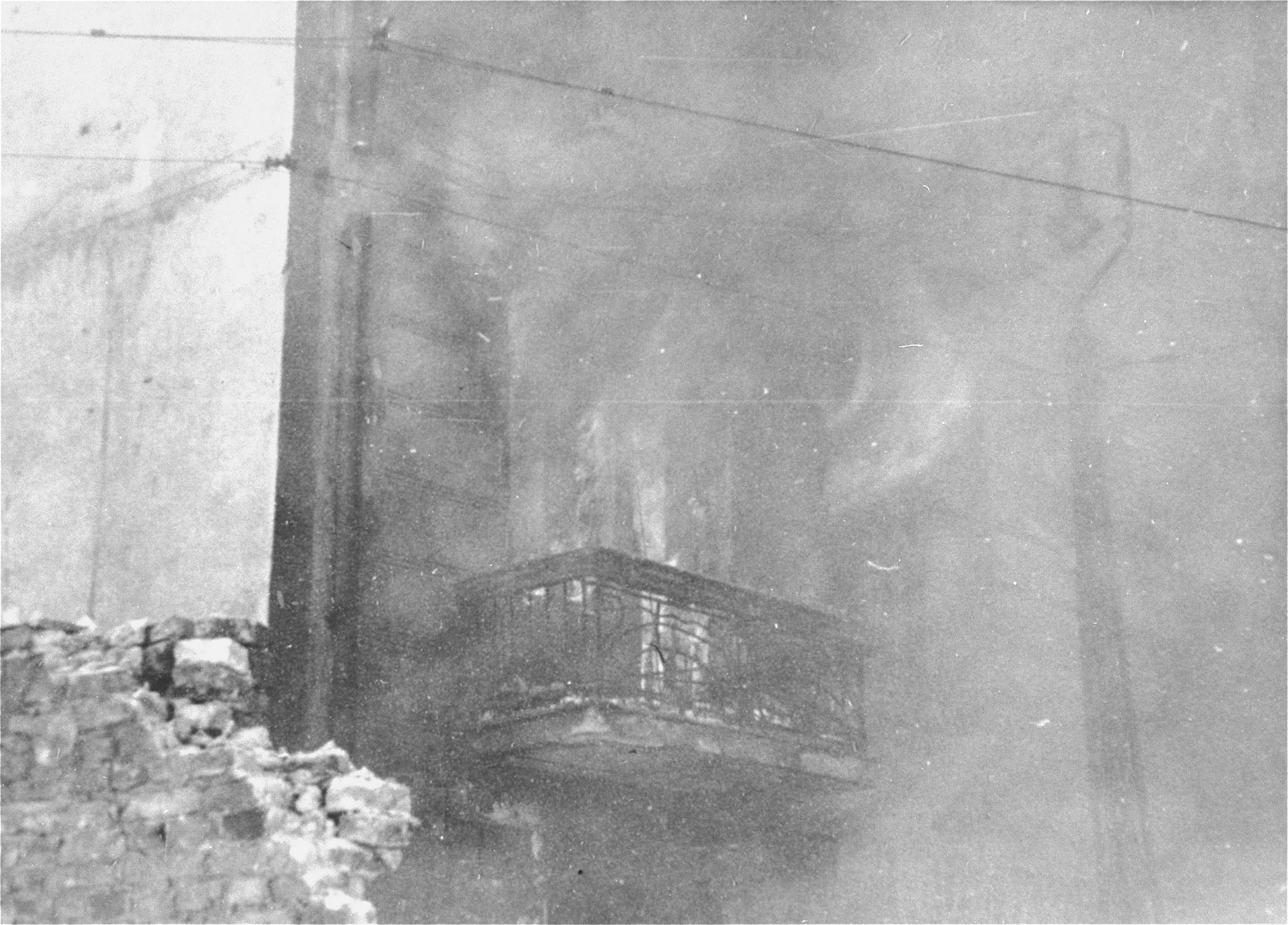 An apartment building razed by the SS burns during the suppression of the Warsaw ghetto uprising.  On the left, a fragment of the Warsaw ghetto wall.