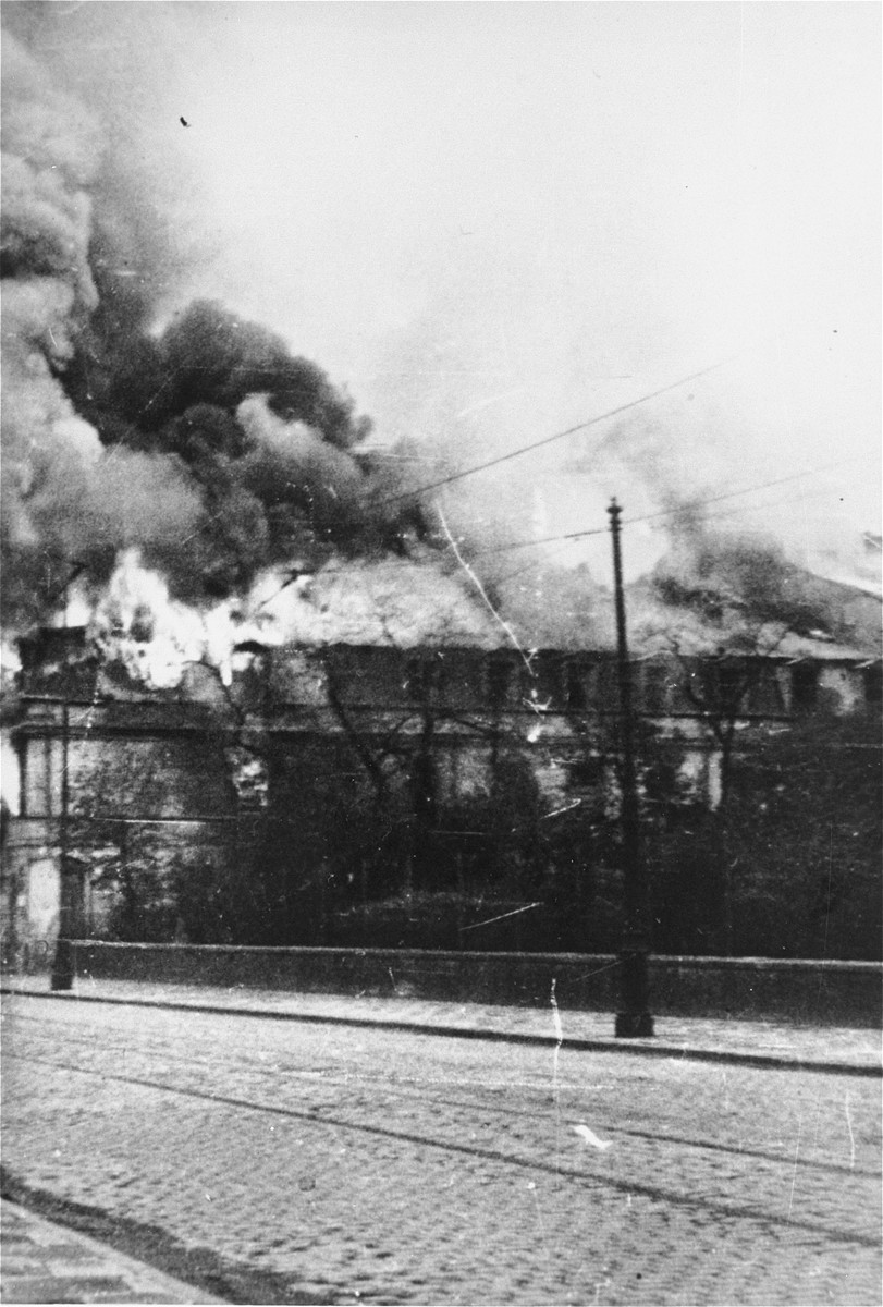 A building razed by the SS burns during the suppression of the Warsaw ghetto uprising.