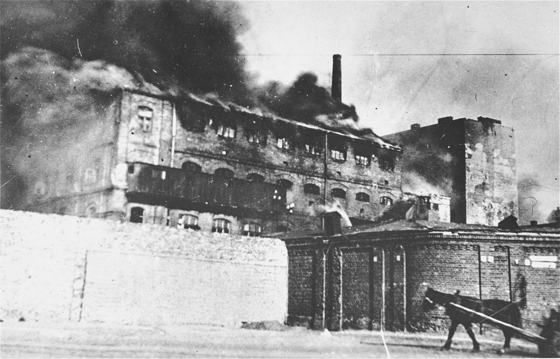 A factory razed by the SS burns during the suppression of the Warsaw ghetto uprising.