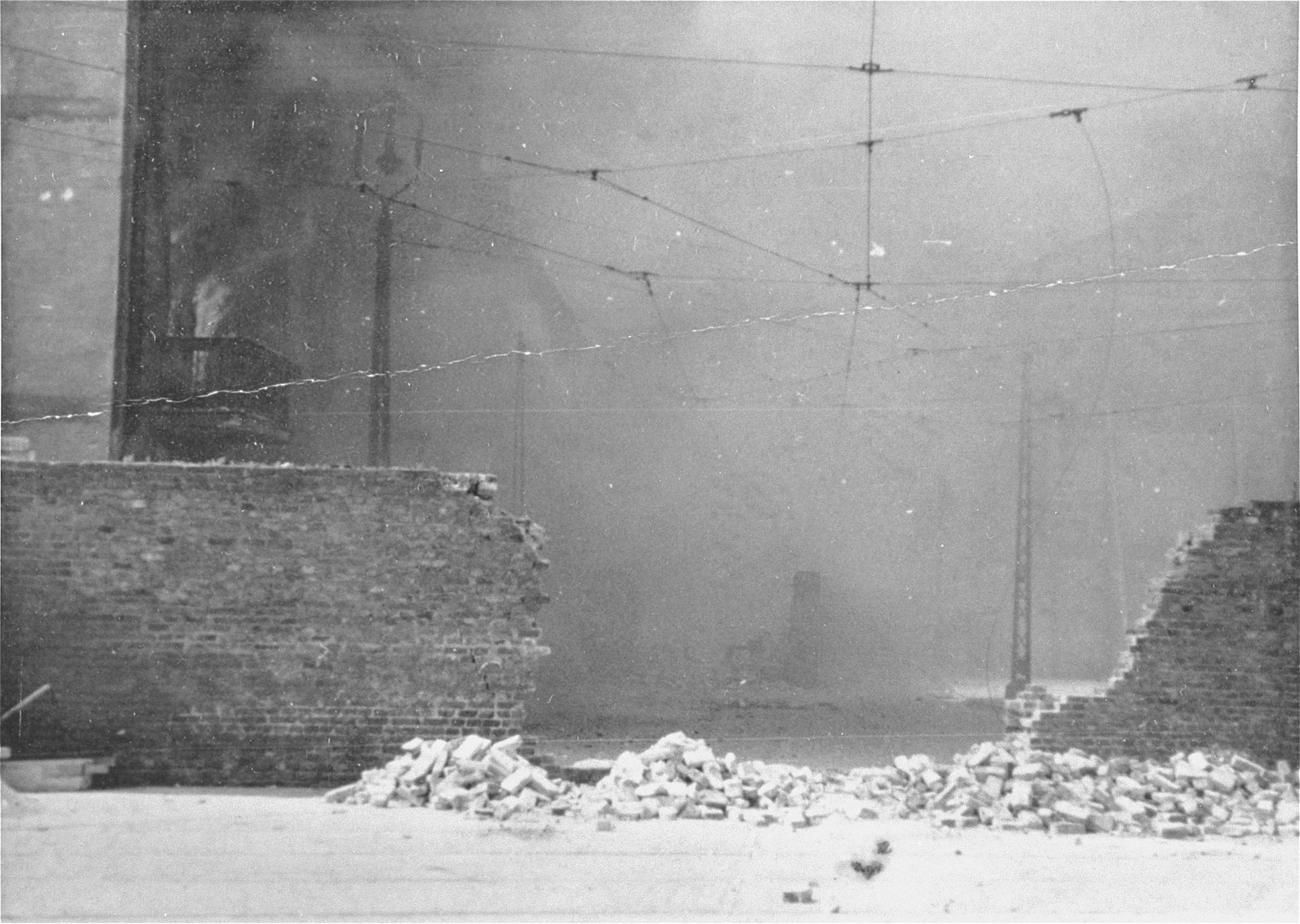Smoke fills the street beyond the breached ghetto wall as apartment buildings razed by the SS burn during the suppression of the Warsaw ghetto uprising.