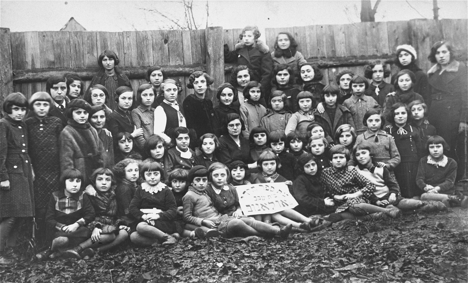 Group portrait of the students at the Beit Yaakov religious school for girls in Ulanow, Poland.    Among those pictured are: Sabina Loew (wearing a fur collar coat in the back row), her sister Udl (wearing glasses in the third row from the front, fifth from the left).  The teacher is Henche Westereich.  Eleven of the pupils survived the war.
